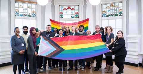 Mayor of Newham with council workers raising the new progress rainbow flat that incorporate the well known rainbow design but additionally now represent trans, black, and ethnic minority communities.