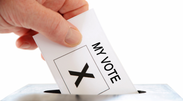 A hand placing a paper with the text 'My Vote' and an X into the opening of a ballot box